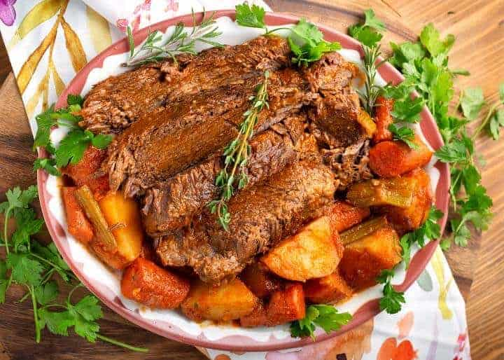 Sliced roast on a platter with the vegetables