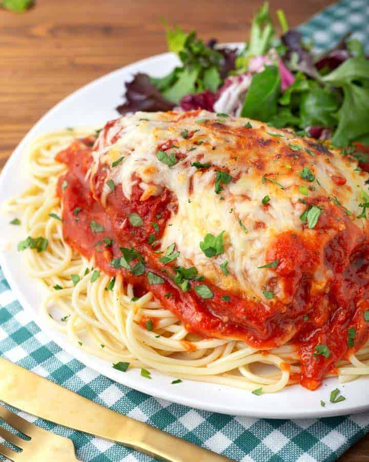 Chicken Parmesan on a white plate with pasta