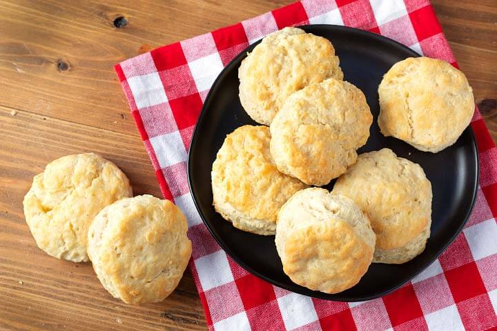 Easy Buttermilk Biscuits looking down on black plate checkered napkin