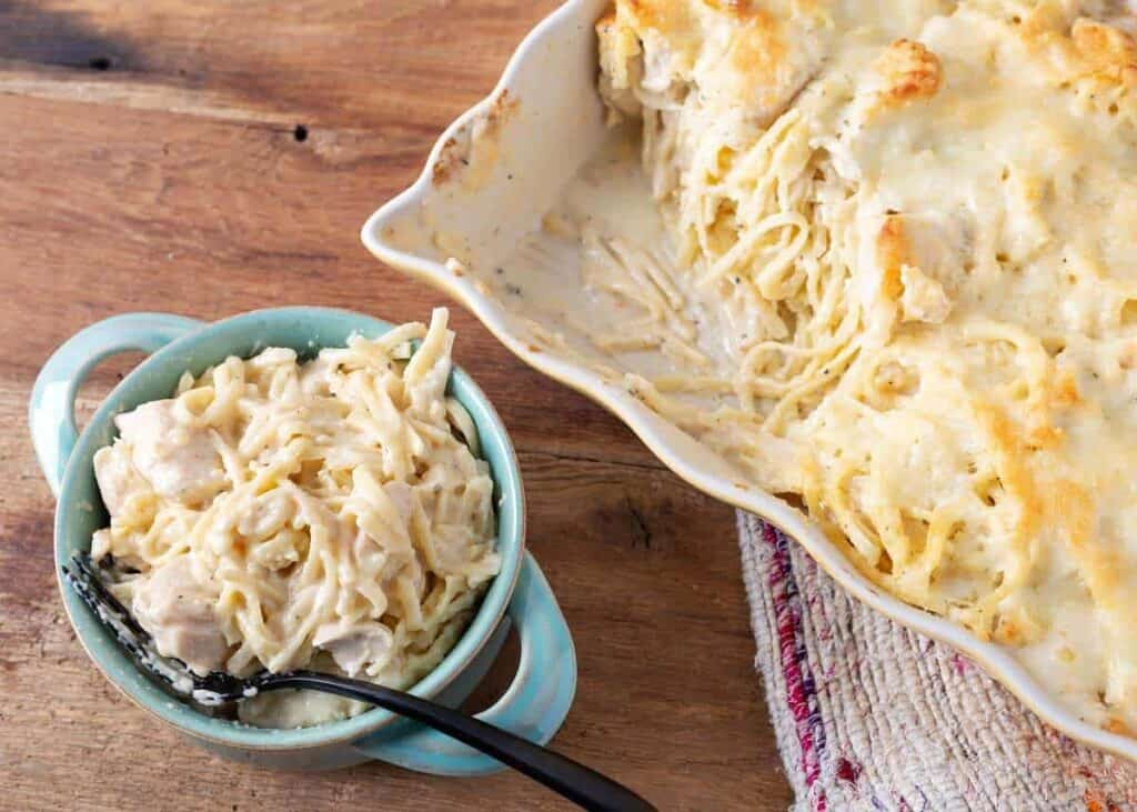 Fettuccine Alfredo Casserole in a baking dish and on a white plate