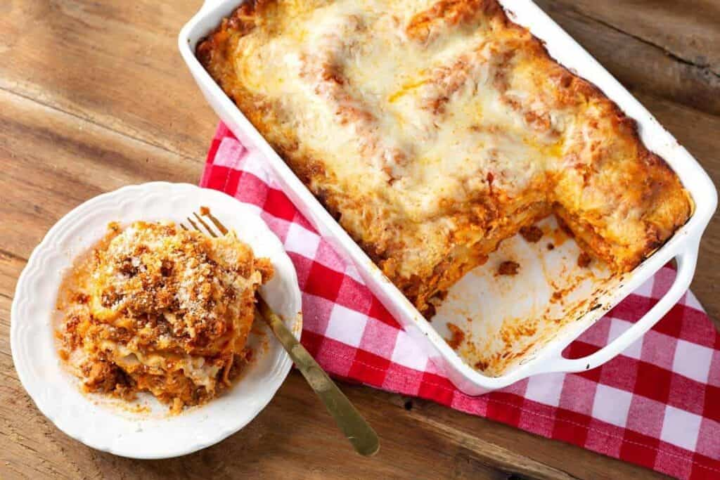 Homemade Lasagna on a white plate and in a white baking dish