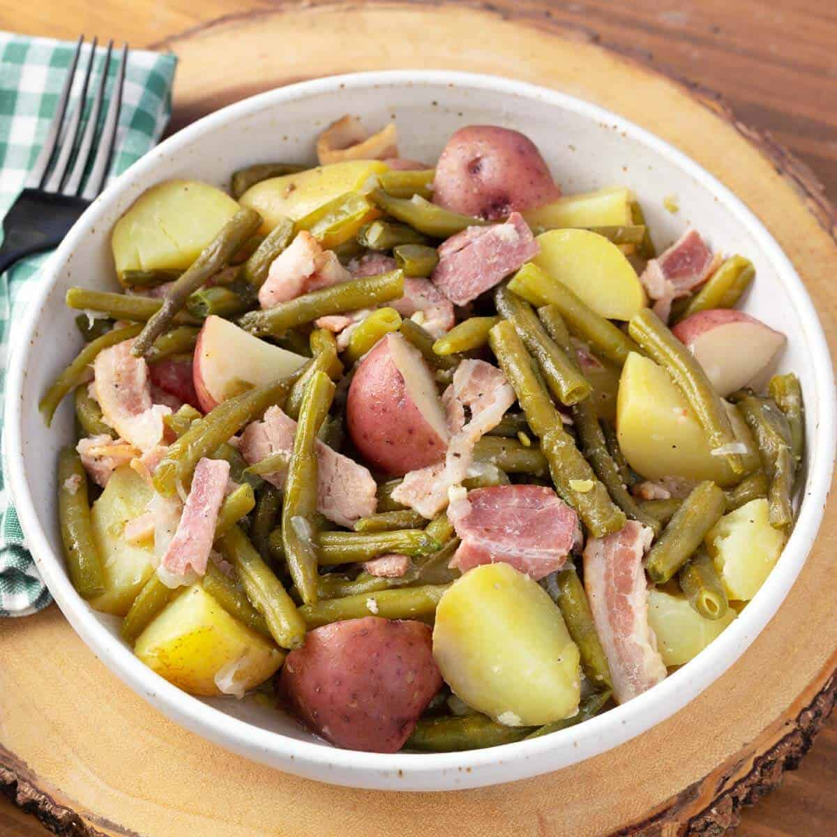 Southern Green Beans Bacon Potatoes in a white bowl on wood