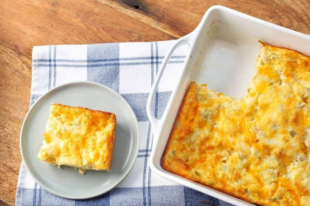 slice of Green Chile Egg Casserole on a plate and in baking dish