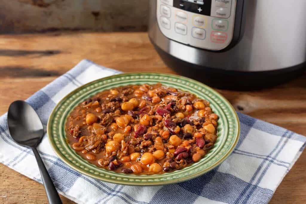 Instant Pot Hamburger Baked Beans in a green bowl, IP in background