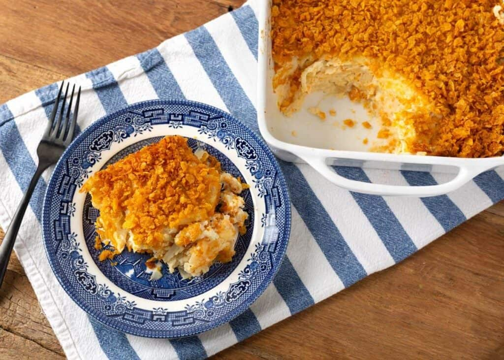 Cheesy Funeral Potatoes on a blue plate and a dish of them