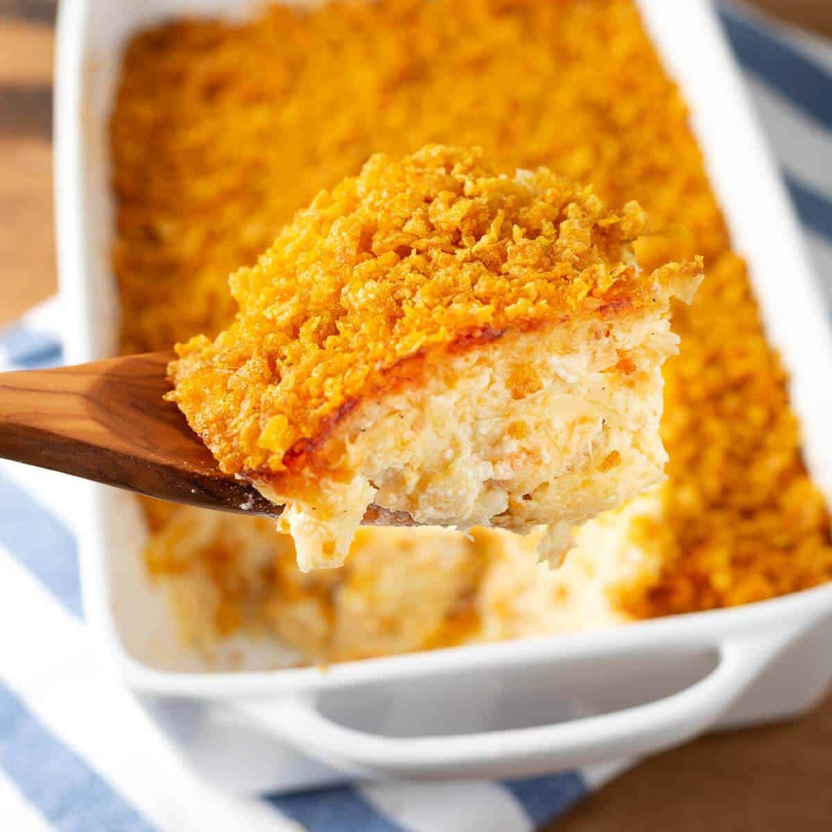 Funeral Potatoes on a wood spoon in front of baking dish