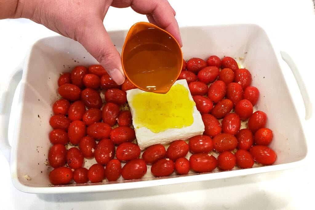 pouring olive oil over feta in white baking dish