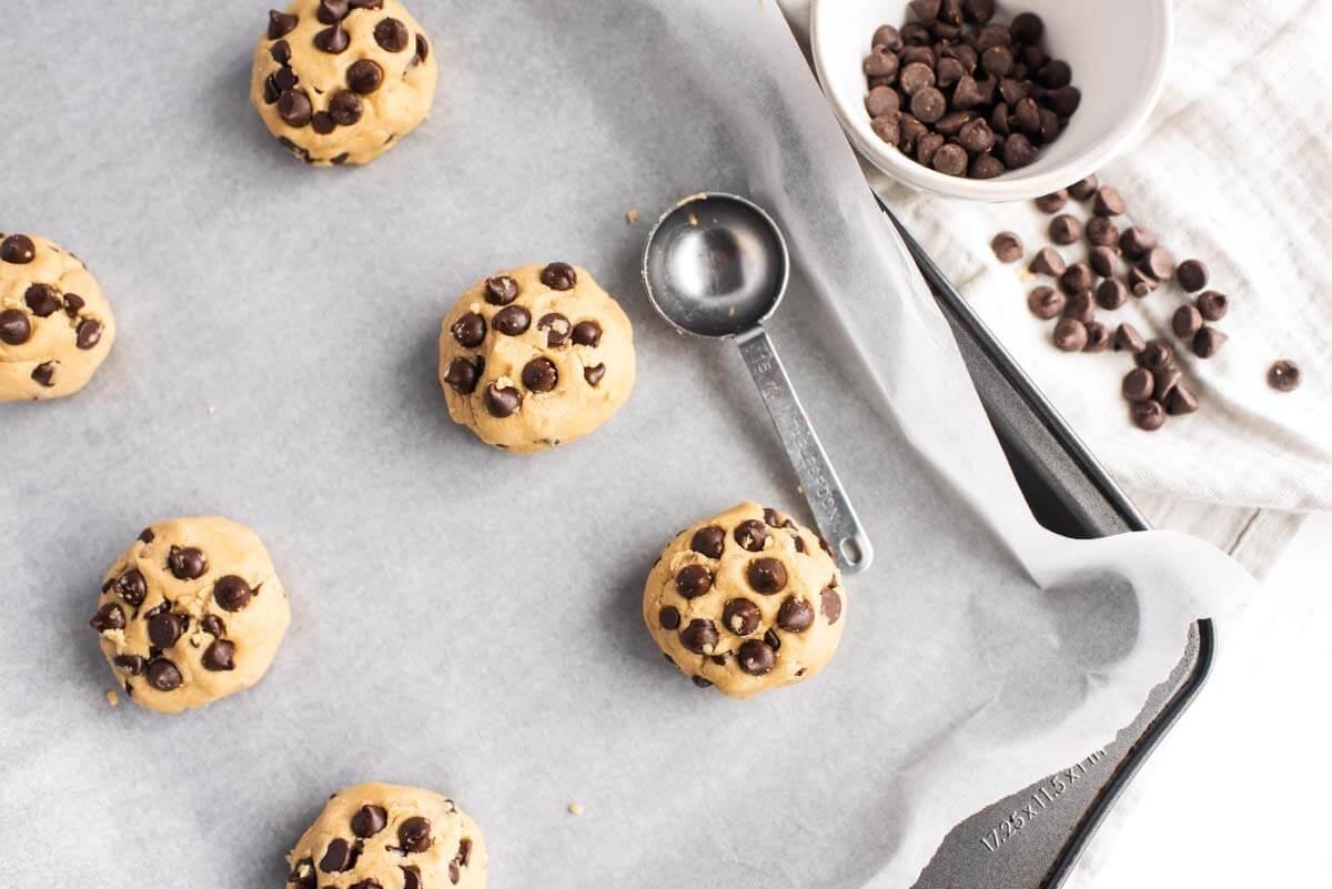 Chocolate Chip Cookie dough balls on baking sheet before baking