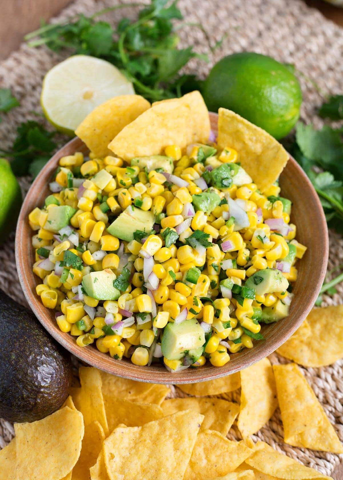 Easy Corn Salsa i a bowl with ingredients around it