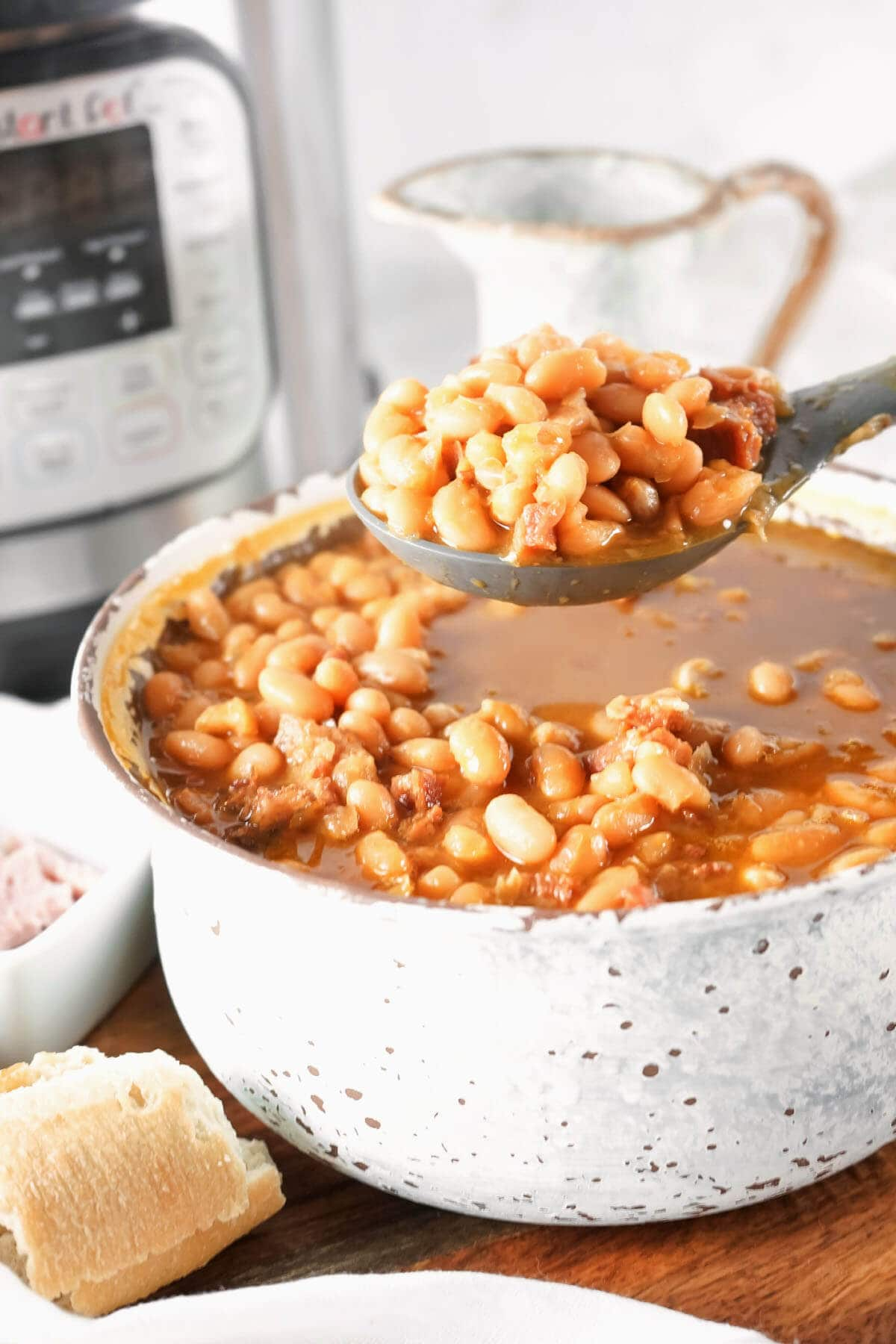 Instant Pot Ham and Bean Soup in a white pot in front of an Instant Pot with a spoonful held above