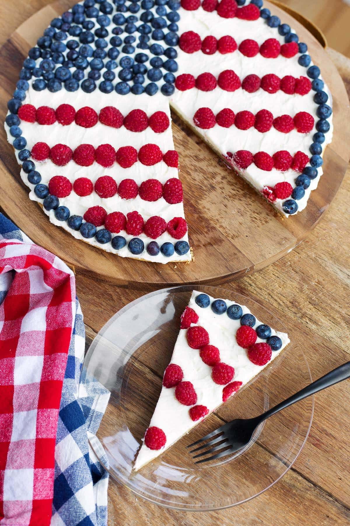Patriotic Fruit Pizza with frosting, blueberries and raspberries on a wood background with a slice on a glass plate