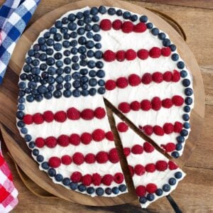 Patriotic Fruit Pizza with frosting, blueberries and raspberries on a wood background