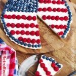 Patriotic Fruit Pizza with a slice out on a wood background
