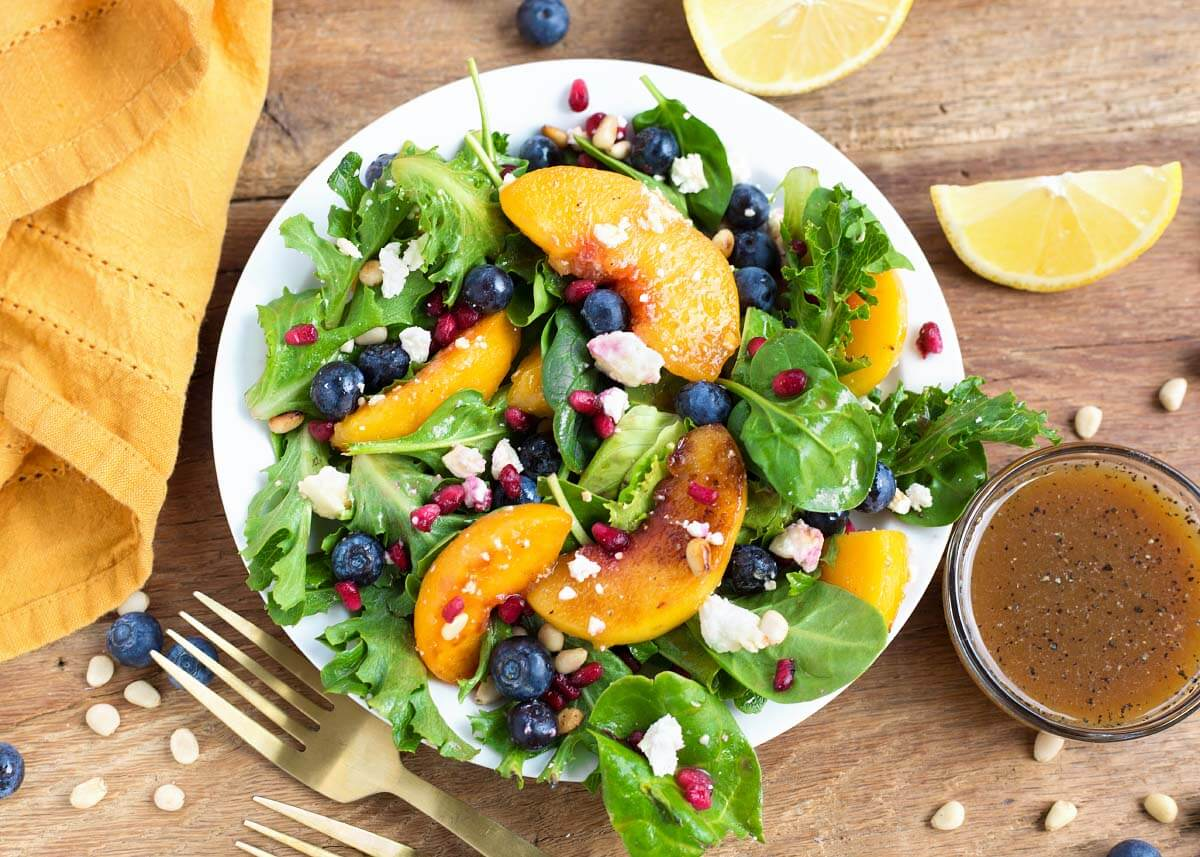 Peach Salad with Blueberries and Feta on a white plate, wood background, from above