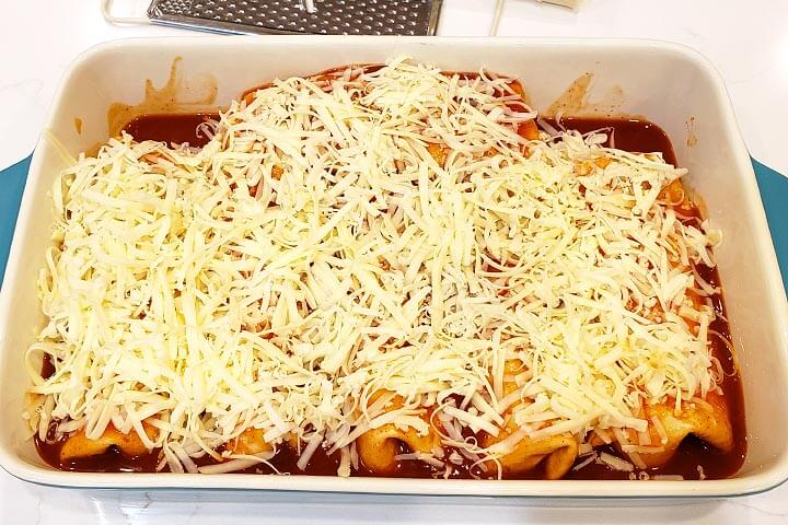 Beef and Bean Burritos in the baking dish with cheese on, ready to get covered and baked