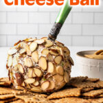 Nutty Bacon Cheese Ball on crackers with a knife