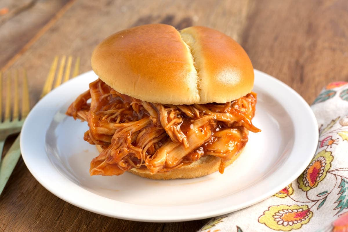 Slow Cooker BBQ Pulled Chicken on a bun on white plate