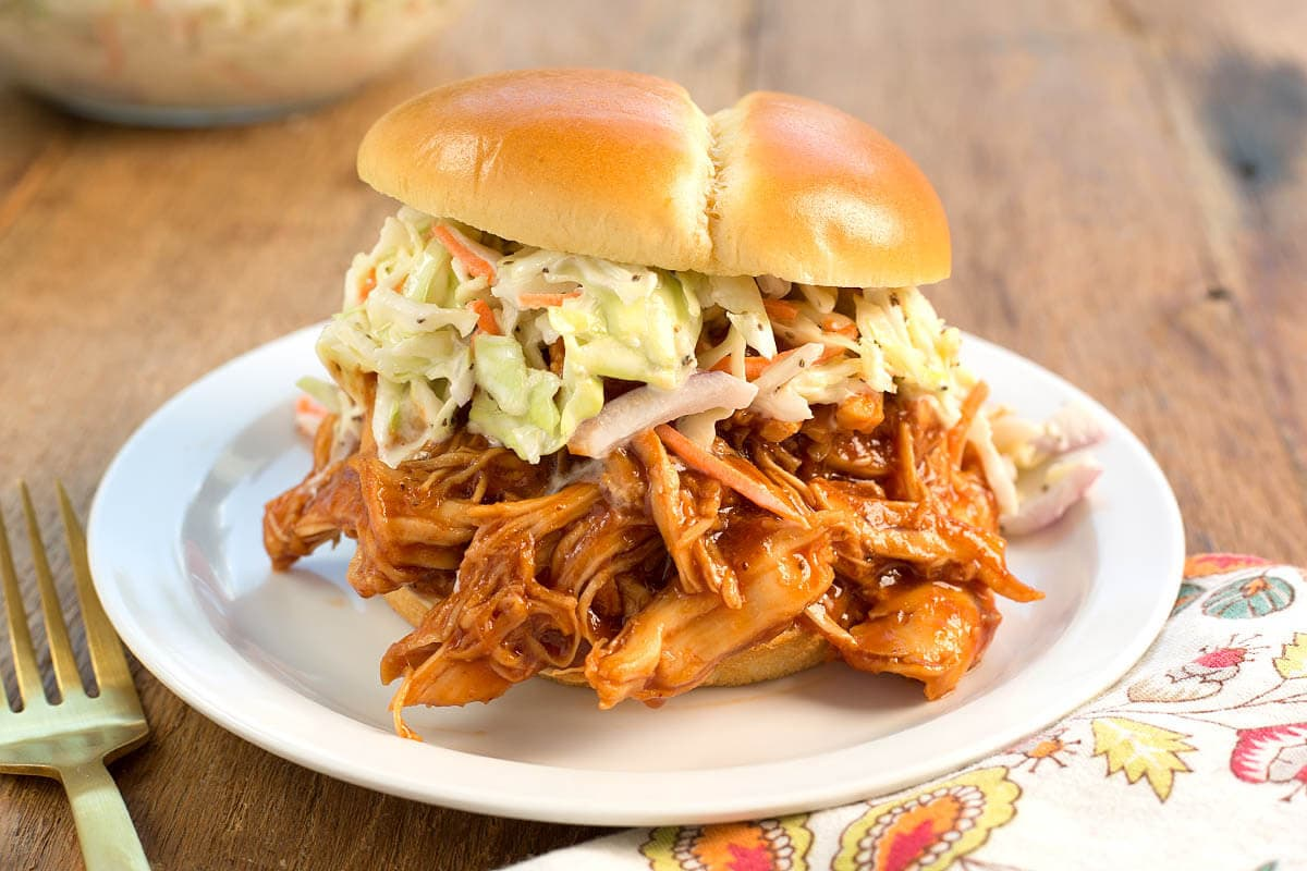 Slow Cooker BBQ Pulled Chicken sandwich with coleslaw on it