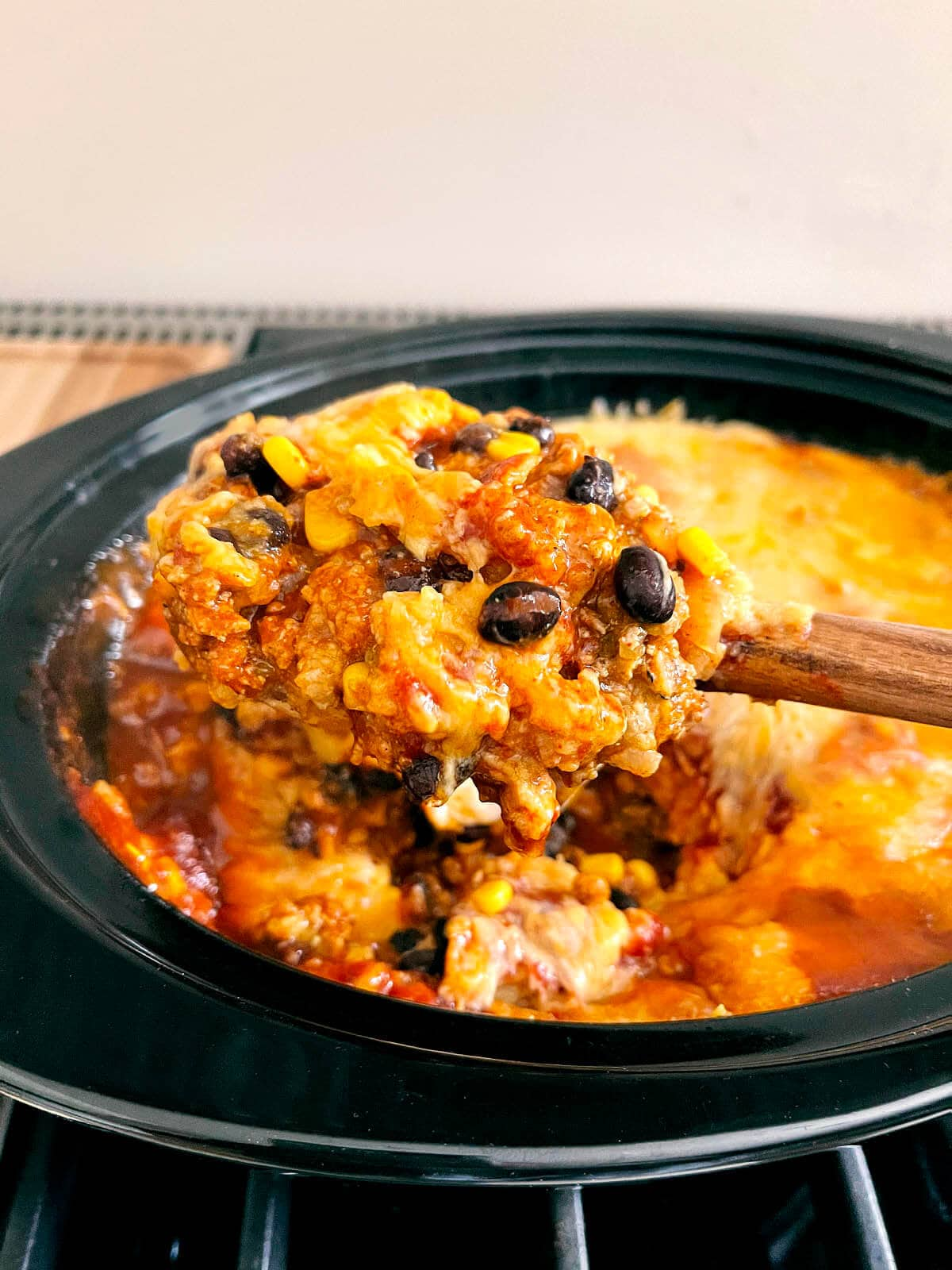 Enchilada Casserole with spoon in black crock