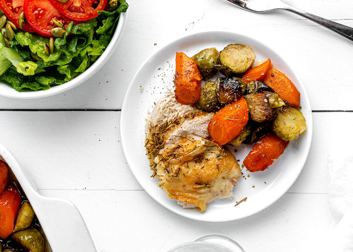 chicken slices and roasted veggies on a white plate