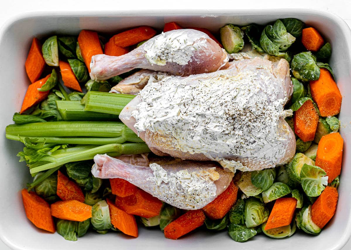 prepared raw chicken in white pan with vegetables