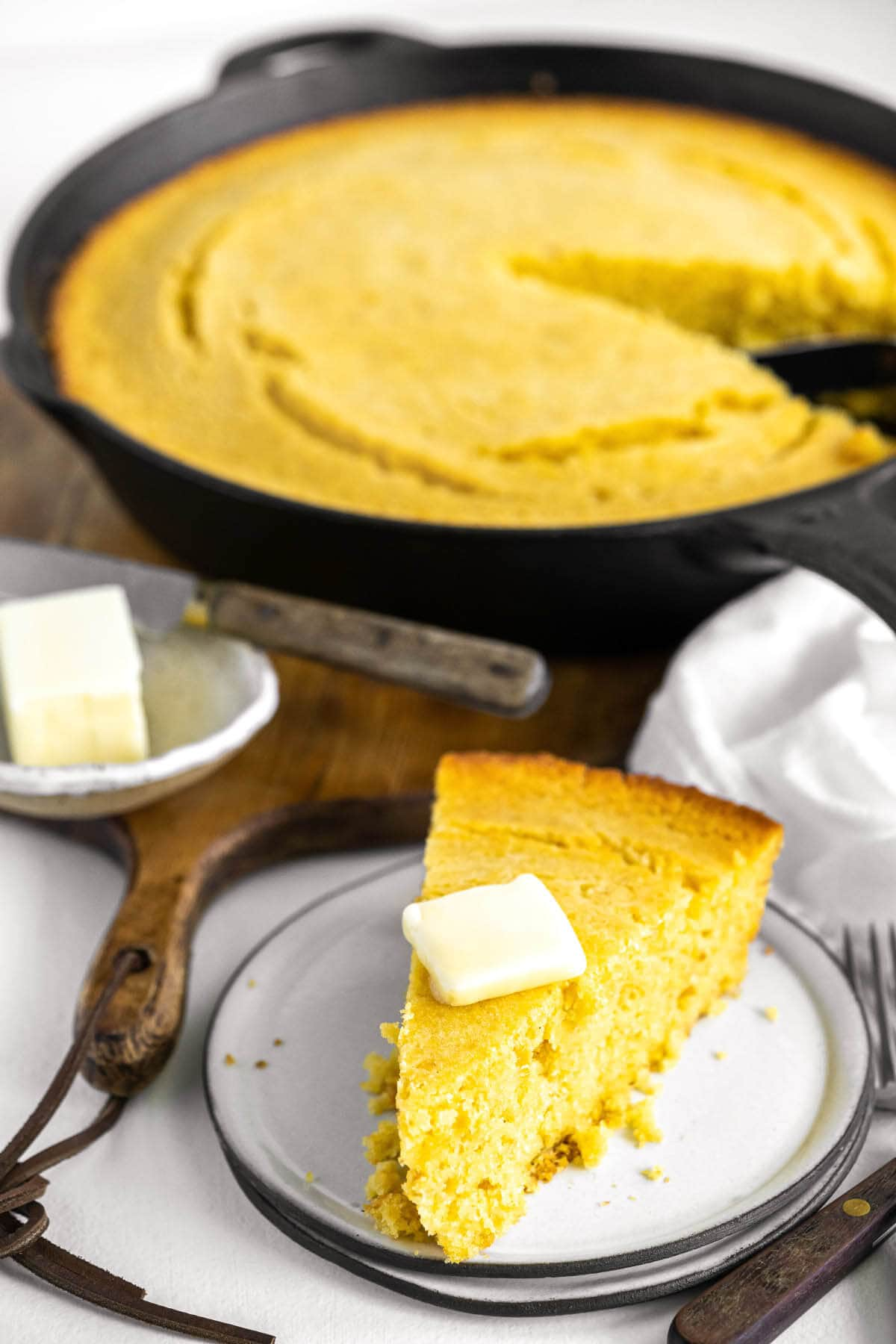 cornbread in the skillet and a slice on a plate.